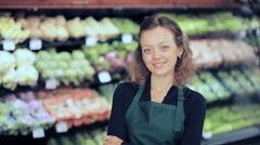Portrait of a grocery store clerk in front of a vegetable section of the store. Stock Footage