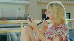 Young woman sitting on a chair balcony, imposes itself makeup Stock Footage