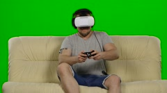 Man wearing virtual reality goggles. Studio shot, white couch. Green screen - stock footage