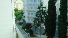 Young woman standing on the balcony of a block of flats, looks into the distance Stock Footage