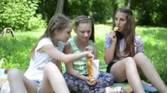 Three girls eat potato chips on a picnic in the park Stock Footage