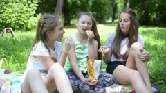 Three girls eat potato chips on a picnic in the park - stock footage