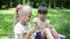 Two girls eat potato chips on a picnic in the park - stock footage