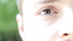 Man opens his brown eyes and smiling. Looking into camera. Stock Footage