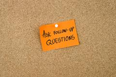 Ask Follow-Up Questions written on orange paper note Stock Photos