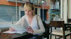Young woman reading a menu in a cafe - stock footage