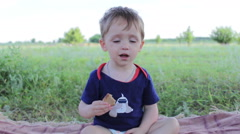 Boy child on the nature eats bread Stock Footage