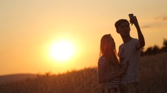 Selfie shoot a girl with a guy at sunset slow motion video Stock Footage