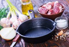 Raw meat and pan on a table Stock Photos