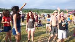 Young pretty girls fans jump dancing enjoying music open air festival - stock footage