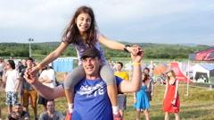 Pretty cute little kid girl sit on father shoulders enjoying open air music fest Stock Footage