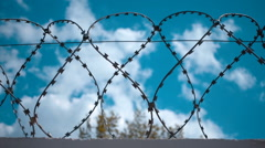Barbed wire at the top of fence against the blue sky with clouds Stock Footage