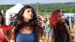 Young pretty girls fans jump dancing raise hands up enjoying music open air fest Stock Footage