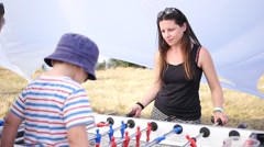 Mother with kid boy play teach a table soccer outdoors slow motion - stock footage