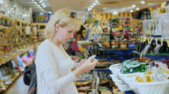 Young woman chooses souvenirs in store for tourists Stock Footage