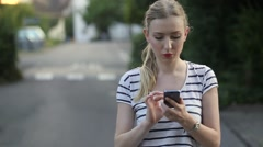 Woman in summer clothes typing on your phone Stock Footage