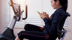 Asian woman with smartphone riding stationary bike in gym. Stock Footage