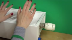Female hands increase radiator temperature and warm hands on it - stock footage