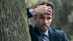 Desperate businessman in a park with hand on forehead - stock footage