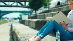 Young woman reading your book and sitting on city quay and looking with smiling Stock Footage