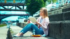 Young woman opening your book and sitting on city quay and looking with smile - stock footage
