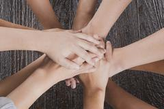 People put hand together for use as unity teamwork concept Stock Photos