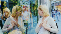 Young woman standing at the windows of women's clothing shop Stock Footage