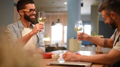 Trendy guys in bar drinking wine and using smartphone - stock footage