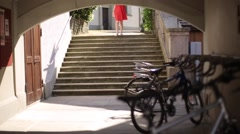 Girl in a red dress with white hair down stairs Stock Footage