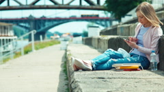 Young woman using your cell phone outdoors sitting on city quay Stock Footage