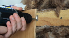 Worker fixes board to wall using electric screwdriver. Mineral wool under board. Stock Footage