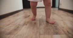 Close-up of baby boy walking his first steps,slow motion Stock Footage