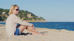 In sun glasses woman sitting on the beach near the sea. He looks at Sea Stock Footage