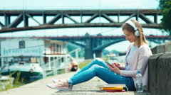 Young adult woman in headphones using mobile phone outdoors on city quay Stock Footage