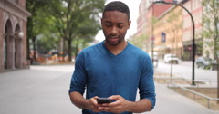 Young African American black man in city walking texting cell phone Stock Footage