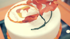 Beautiful round cake of white color decorated with flowers at the top - stock footage