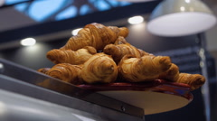 Croissants of brown and golden color on a tray in a coffee house Stock Footage