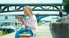 Young adult woman using mobile phone outdoors on city quay - stock footage