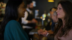 4K Bar staff serving drinks & female friends chatting in city bar. Stock Footage