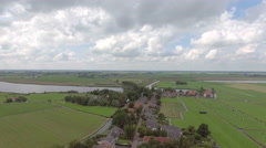 Aerial of small village in Holland by river Stock Footage