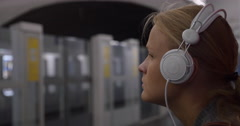 Woman listening to music in subway Stock Footage