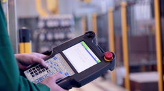 Worker operates with Robotic Arm Loading and assembling products. Industrial - stock footage