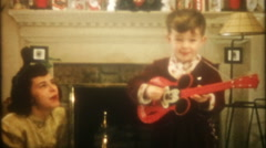 3416 young boy gets a Mickey Mouse guitar on Christmas-vintage film home movie Stock Footage