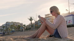 Young woman enjoys the tablet in the resort town. Sitting on the sand on the Stock Footage