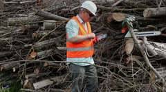 Lumberjack using tablet PC at the pile of branches - stock footage