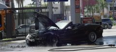 A burned out convertible smolders at a gas station. Slow motion. Stock Footage