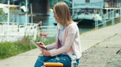 Young adult woman with headphones using tablet pc outdoors near river - stock footage