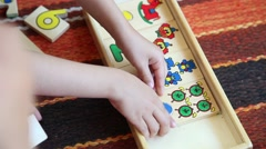 Kid playing with geometric pieces board game Stock Footage