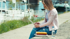 Young adult woman with headphones using tablet pc outdoors near river. Smiling - stock footage