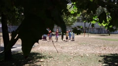Kids playing in a playground unfocused, focus on tree, slider shot - stock footage